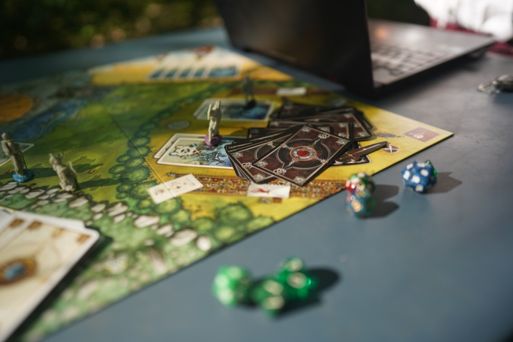Several sets of colored dice and board game cards are seen next to a board, which is on a table next to a laptop.