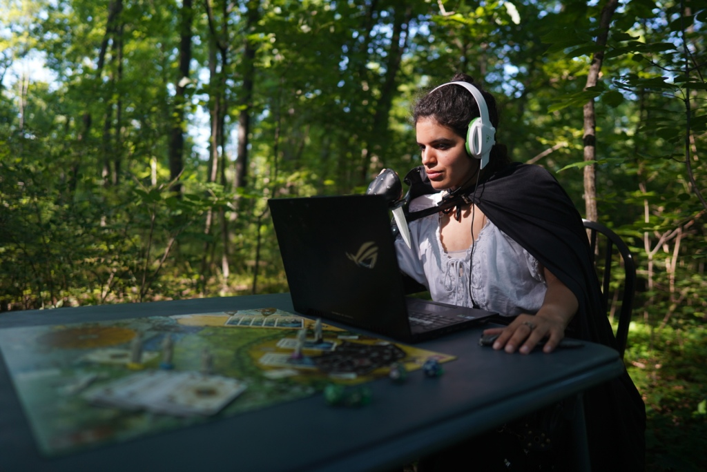 Soph sits at a laptop in front of a game board. She is dressed as a rogue in cape, bracers, knife, with a white headset. She sits in a forest.