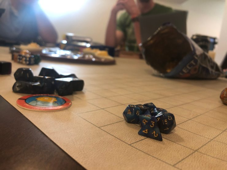 A stack of role-playing-game dice, dark blue. The dice are stacked on a gridlike board.