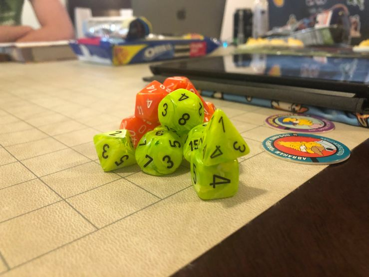 A stack of role-playing-game dice, lime green and orange. The dice are stacked on a gridlike board in front of a laptop.
