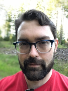 Headshot of Logan Bonner, a white-presenting man wearing glasses and a red t-shirt