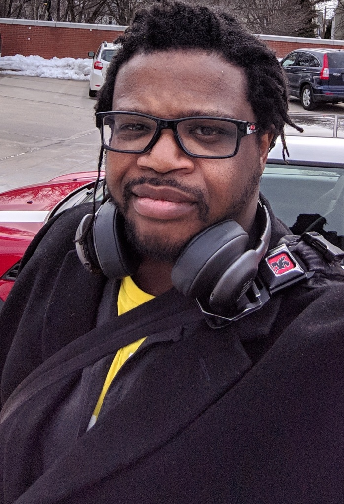 Quinn Murphy looks at the camera with headphones around his neck. Quinn is a male-presenting person of color with glasses, wearing a winter coat.